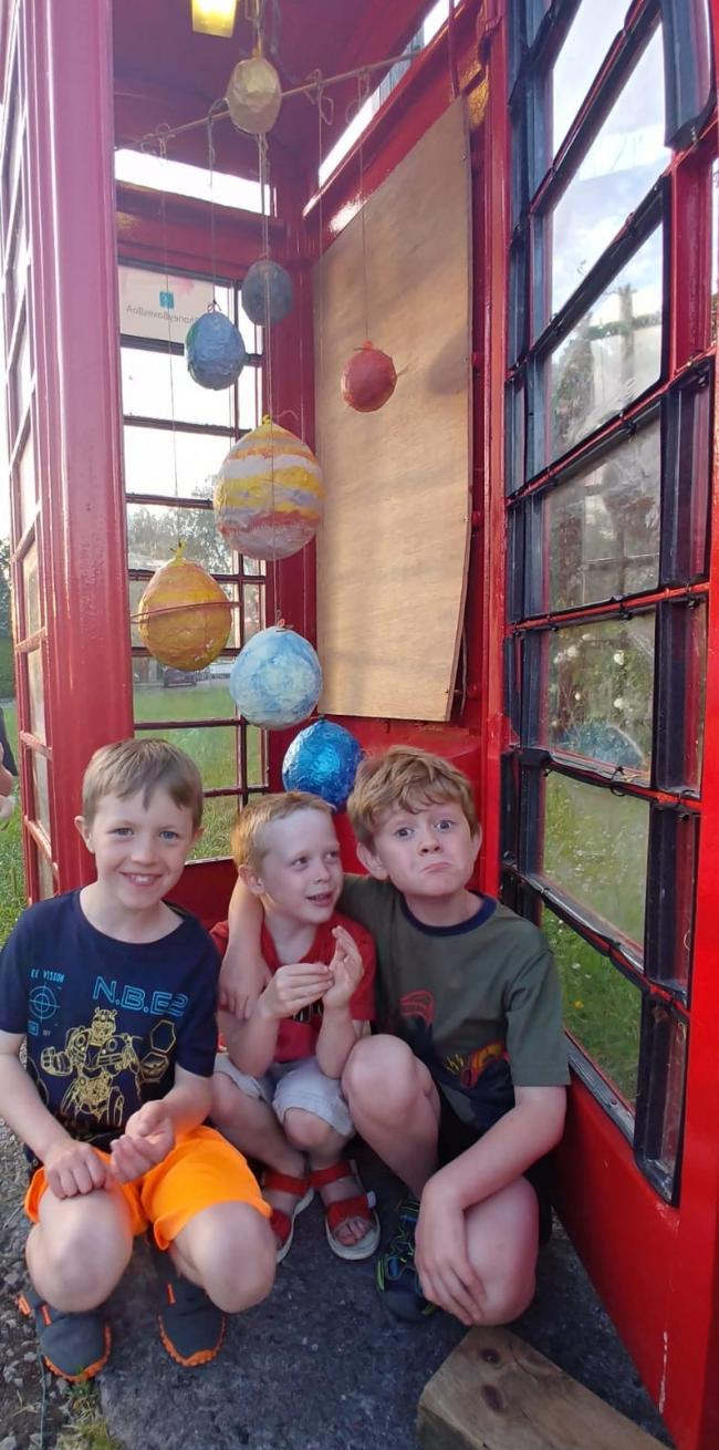 Jamie, Peter and William with their solar system in the phone box.