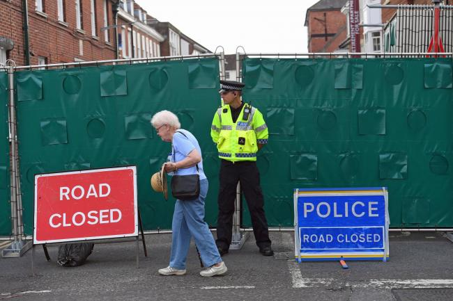A police officer stands in front of screens erected in Rollestone Street, Salisbury, Wiltshire, where counter-terrorism police are investigating after a couple were left in a critical condition when they were exposed to the nerve agent Novichok. Photo: St