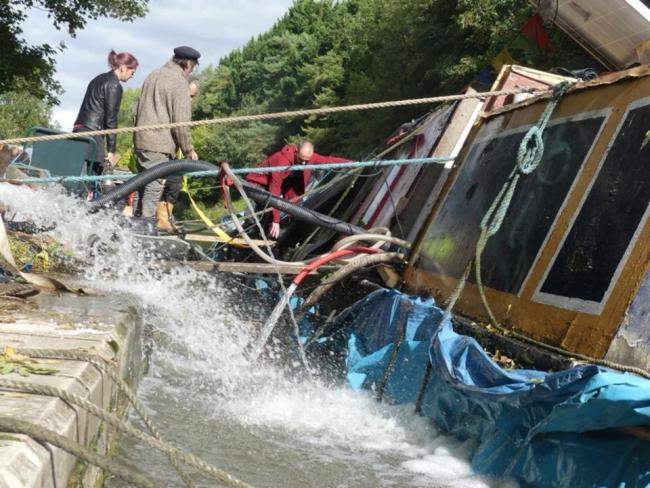 Canal boaters try to rescue George Ward's 90-year-old narrowboat, Celtic, after it was swamped by the wash from two hire boats Photo: Dru Marland