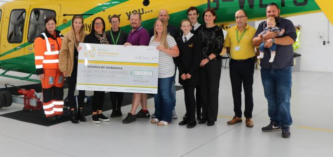 Members of Recycle for Wiltshire Air Ambulance presenting the cheque at Wiltshire Air Ambulance's airbase.