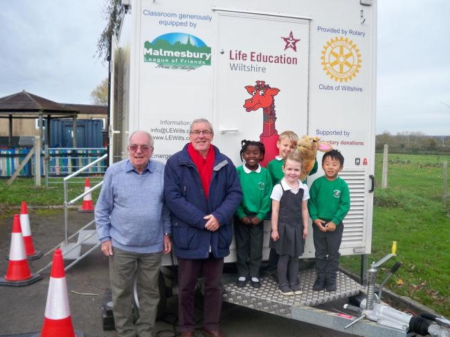 Rotarian Ray Sanderson (left) with Malmesbury League of Friends chairman David Hide and children from Hullavington School in front of the Life Education Classroom.