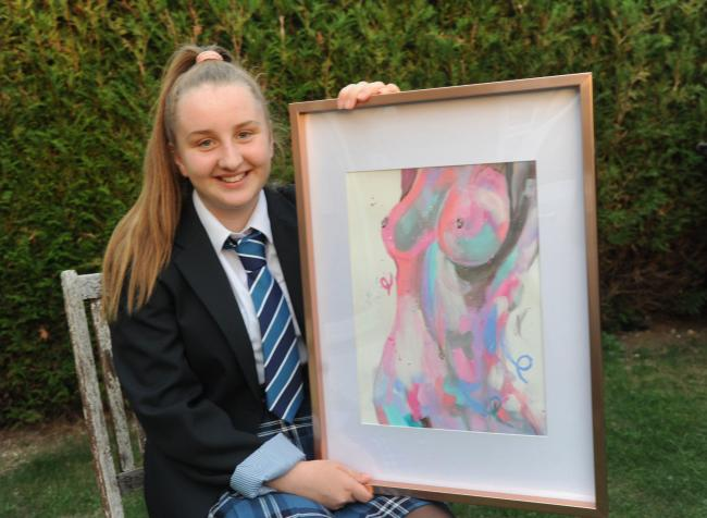 Raising money for charity Grace sits with her Art work that has raised £970 for Cancer Research UK