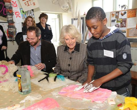 The Duchess of Cornwall learns about felting with student Ashley and charity founder Jamie Feilden