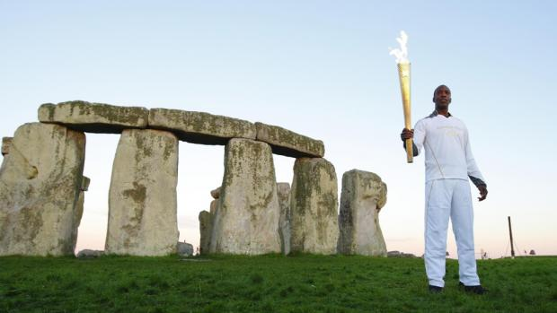 Olympic sprinter Michael Johnson holds the flame at Stonehenge on Thursday morning