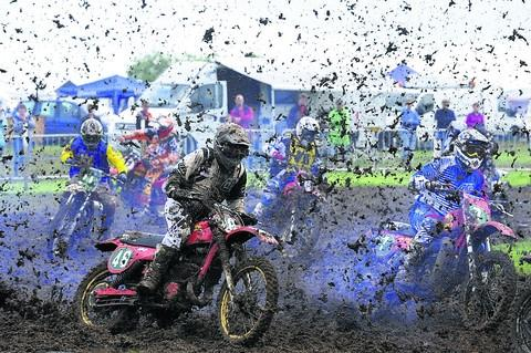 Riders send the mud flying while throttling out of a bend in the 125/250cc race at Farleigh Castle's King of the Castle meeting on Sunday