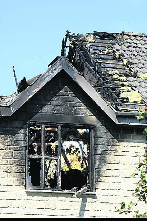 A damaged window after the fire which gutted a house in Butlers Close, Sherston