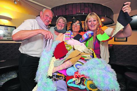 Knitters at the Rising Sun – John Purnell, Annie Skinner, Liz Northeast and Emily Knight – find out how far they have to go with their giant scarf, which should eventually stretch from the pub to Dorothy House, Winsley, 1.9 miles away