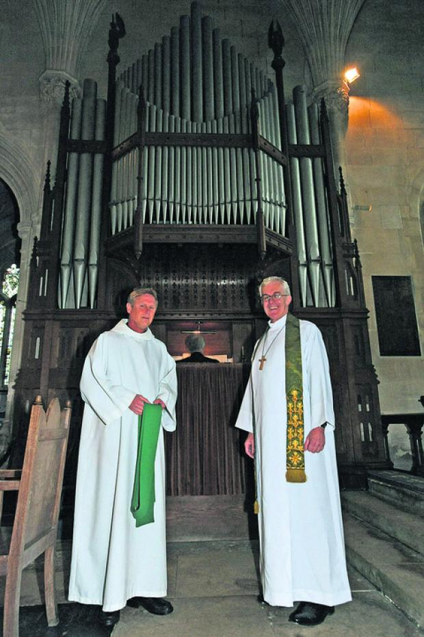 The Rev Julian Parker and the Bishop of Ramsbury, the Rt Rev Edward Condry, with the rebuilt church organ inside Steeple Ashton Church