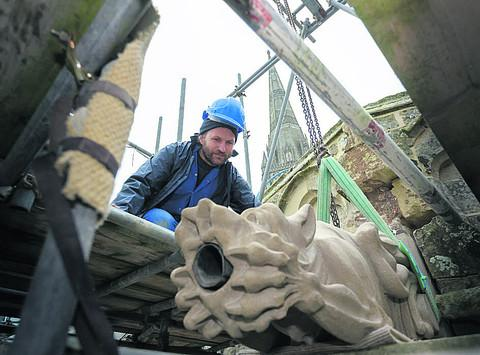 Matt Barton gently lowers the gargoyle in place