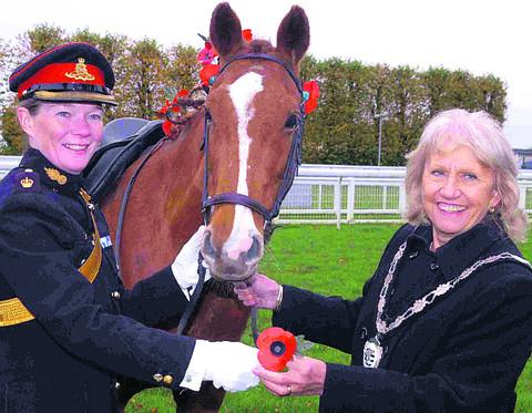 Major Erica Bridge presents a poppy to Coun Christine Crisp