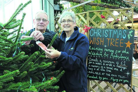 John and Sandra Phillips, volunteers with Wiltshire Air Ambulance, with the Christmas Wish Tree at Lowden Garden Centre