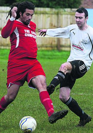 Calne's Mark Dolman (white) gets a challenge in on Purton's Devan Bryan during the Lilywhites' 3-0 win in the Wiltshire League Premier Division on Saturday