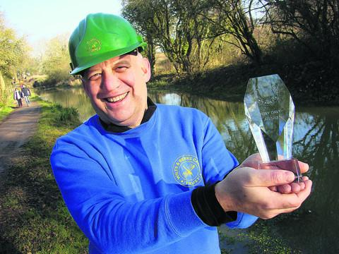 Derek Flexer with the Tony Davy Award next to the restored canal between Melksham and Chippenham