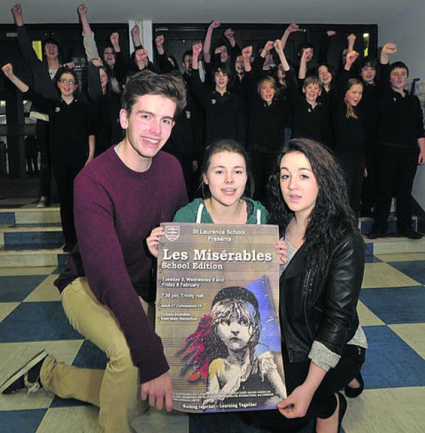 Front, Lewis Bly as Javert, Rosie Morgan as Cosette and Naomi Baker (right) as Eponine with supporting cast members singing behind