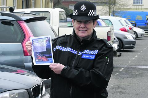 Inspector Lisette Harvey with a flyer warning motorists not to leave valuables in the car