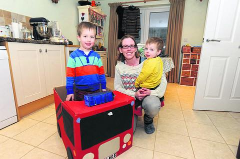 Jen Gale with son William, four, playing in a fire engine made from a cardboard box, while Samuel, one, wears hand-me-down clothes
