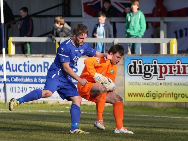 Chippenham Town striker Tom Knighton puts Barwell keeper Liam Castle under pressure (Picture by Robin Foster)