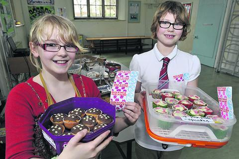 Siana Goodwin, left, and Esther Frawley with cakes for their cancer charities bake sale