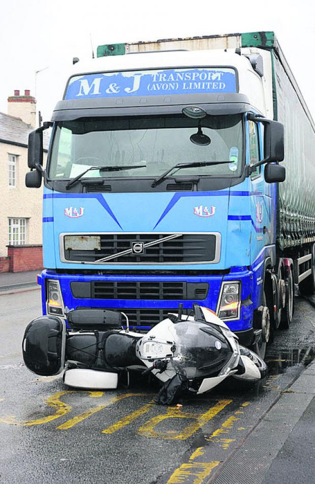The BMW motorbike wedged under the grille of the lorry cab