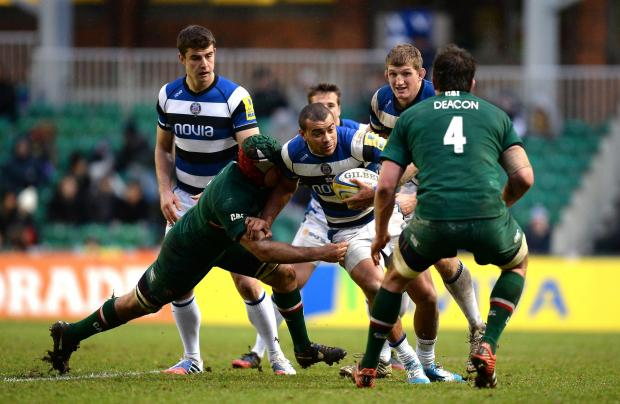 Jonathan Joseph (centre) is tackled by Leicester Tigers' Julian Salvi (left)