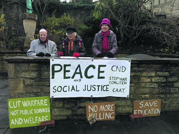Stand Up For Peace group members, from left, Beatrice Valatin, Virginia Brookes and Chris Sylvester in action with signs