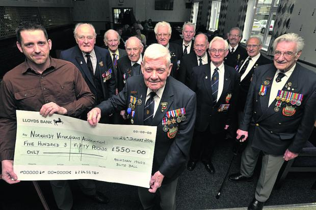 Wiltshire Times: Bob Conway, chairman of the Wiltshire Normandy Veterans Association, receives a cheque from Melksham Blitz Ball organiser Jason Close
