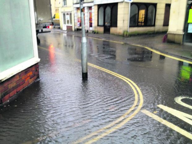 Water overflows from a blocked drain at the corner of Duke Street and Church Street, Trowbridge, today