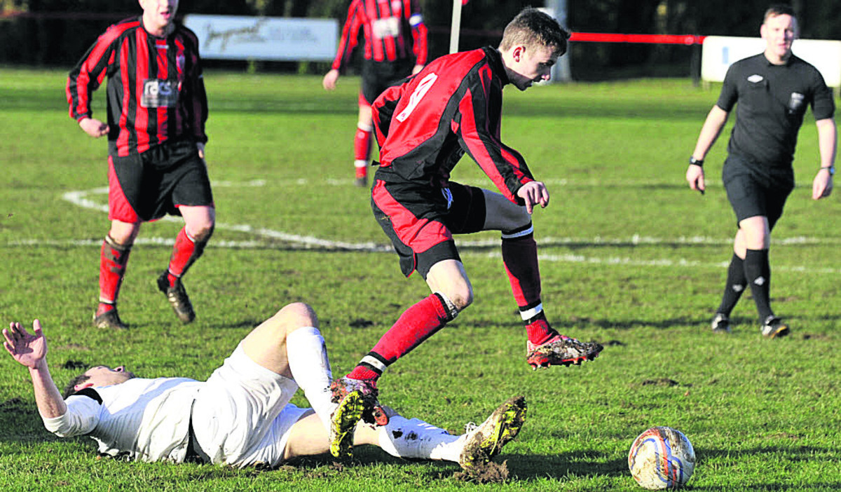 Warminster Town's Jack Miluk avoids a sliding tackle from Roman Glass defender Nat Abrahams