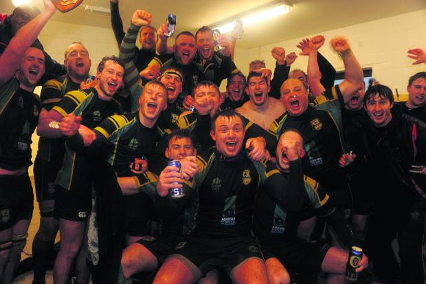 Trowbridge's players start the celebrations in the sanctuary of their changing room after their Southern Counties Intermediate Cup final victory over Bletchley at Doric Park in foul weather conditions on Saturday
