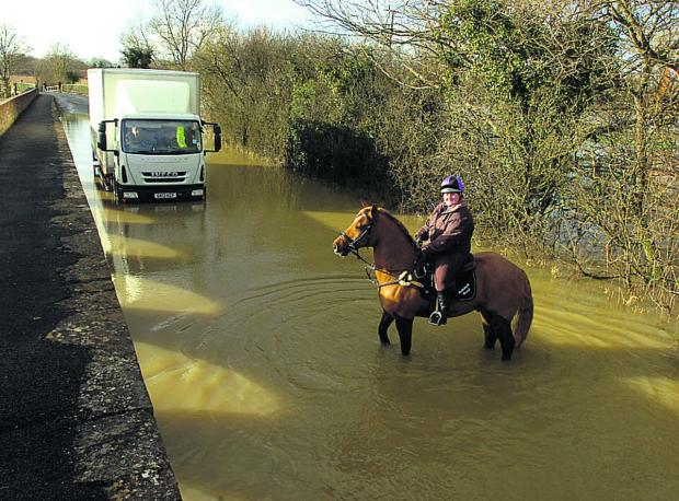 Wiltshire Times: Rider Rebekah Read and her horse cope with floods at Langley Burrell, near Chippenham, today