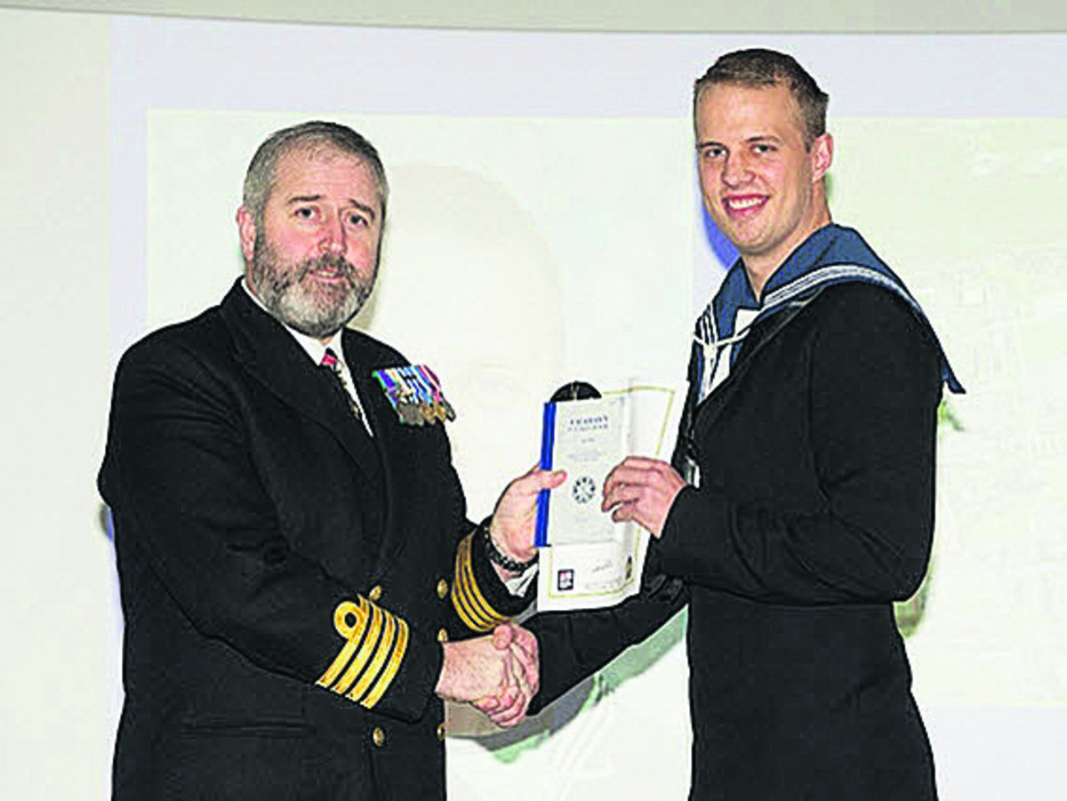 Able Seaman Johns-Lines  presented with his certificate by Captain Steve Dainton, Captain of the Maritime Warfare School.