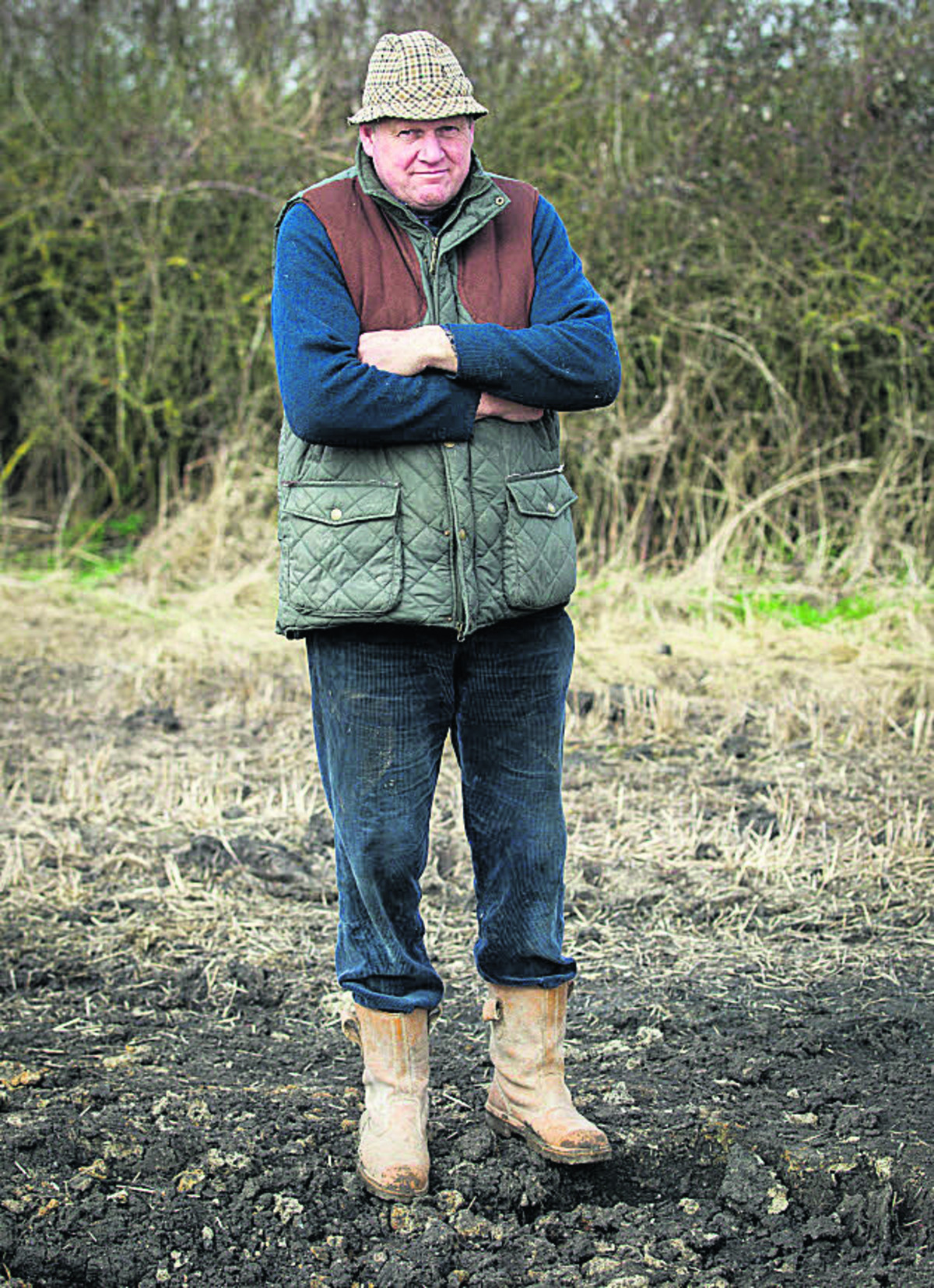 Andrew Snook next to the crater on his farm at Patney after an Army shell landed in a field near the main Penzance-Paddington railway line