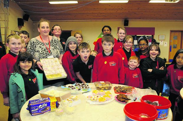 Chairman of the friends Caroline Morris with cakes being snapped up by pupils at Oasis Academy in Longmeadow, Trowbridge