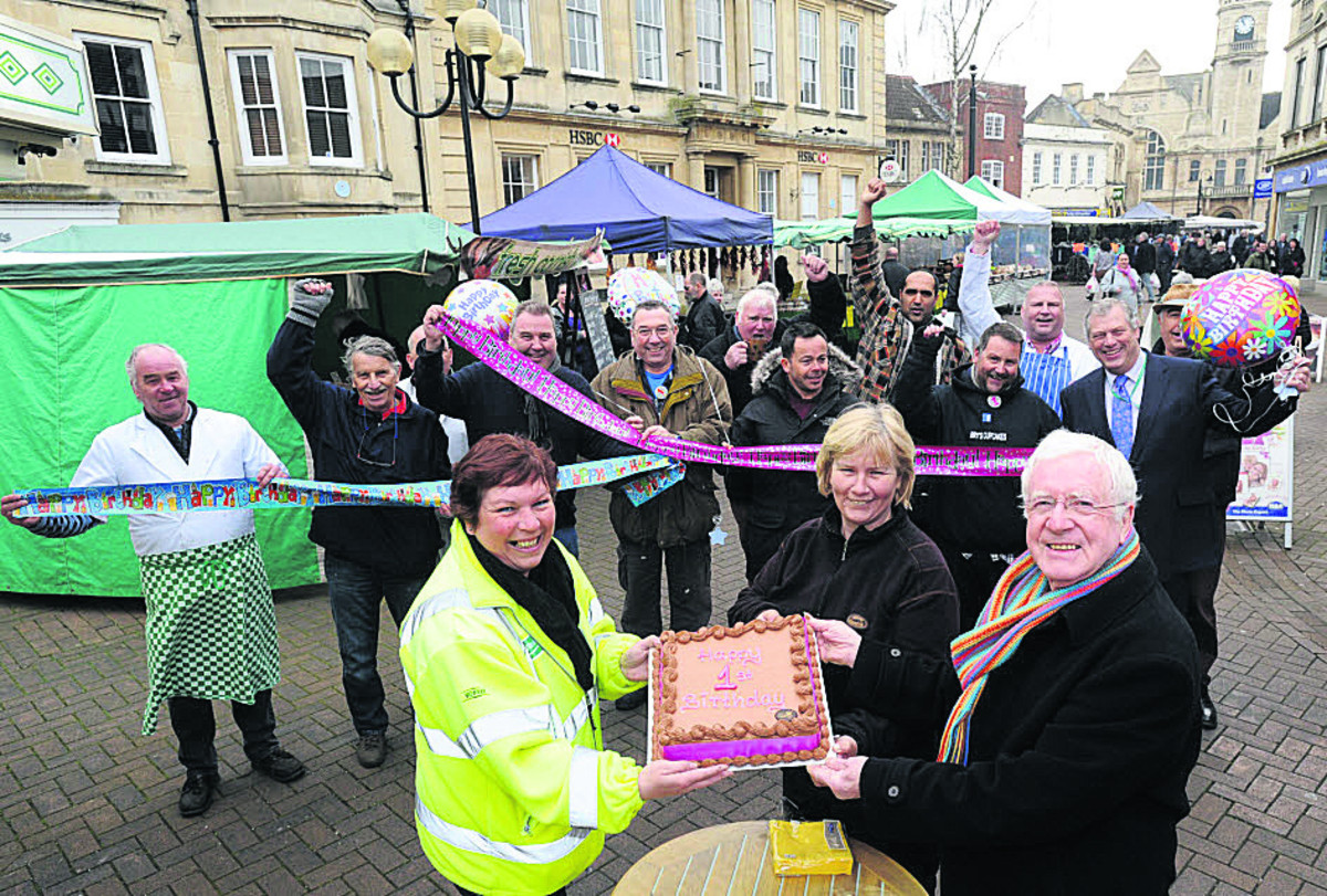 Wiltshire Council market officer Lisa McKee, trader Karen Miller Ward who made the cake, and David Baker of the Town Team along with traders celebrating the success of the market                                                               Photo: Trevor