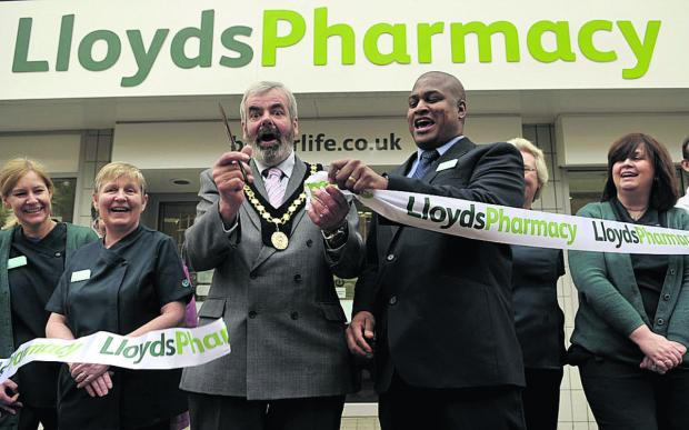 Deputy mayor Clive Blackmore cuts the ribbon at the new improved Lloyds Pharmacy in Fore Street, Trowbridge, with the help of store manager Marlon Marballie, while staff members Helen, Jan,  Angela and Jackie cheer them on