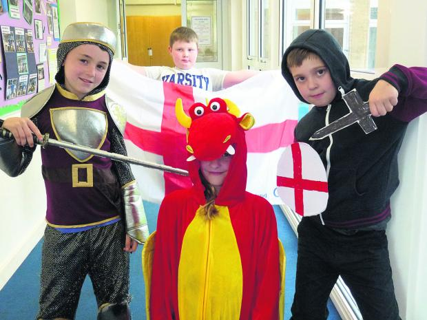 Put him to the sword...valiant knights Ben, Kierran and Kaden prepare to take on Lottie, as the red dragon, as part of the St George's Day celebration at Westbury Junior School.