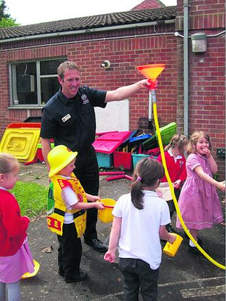 Fire Officer Martin Waker and Bratton Primary pupils douse a make-believe fire as part of their Health and Safety Week