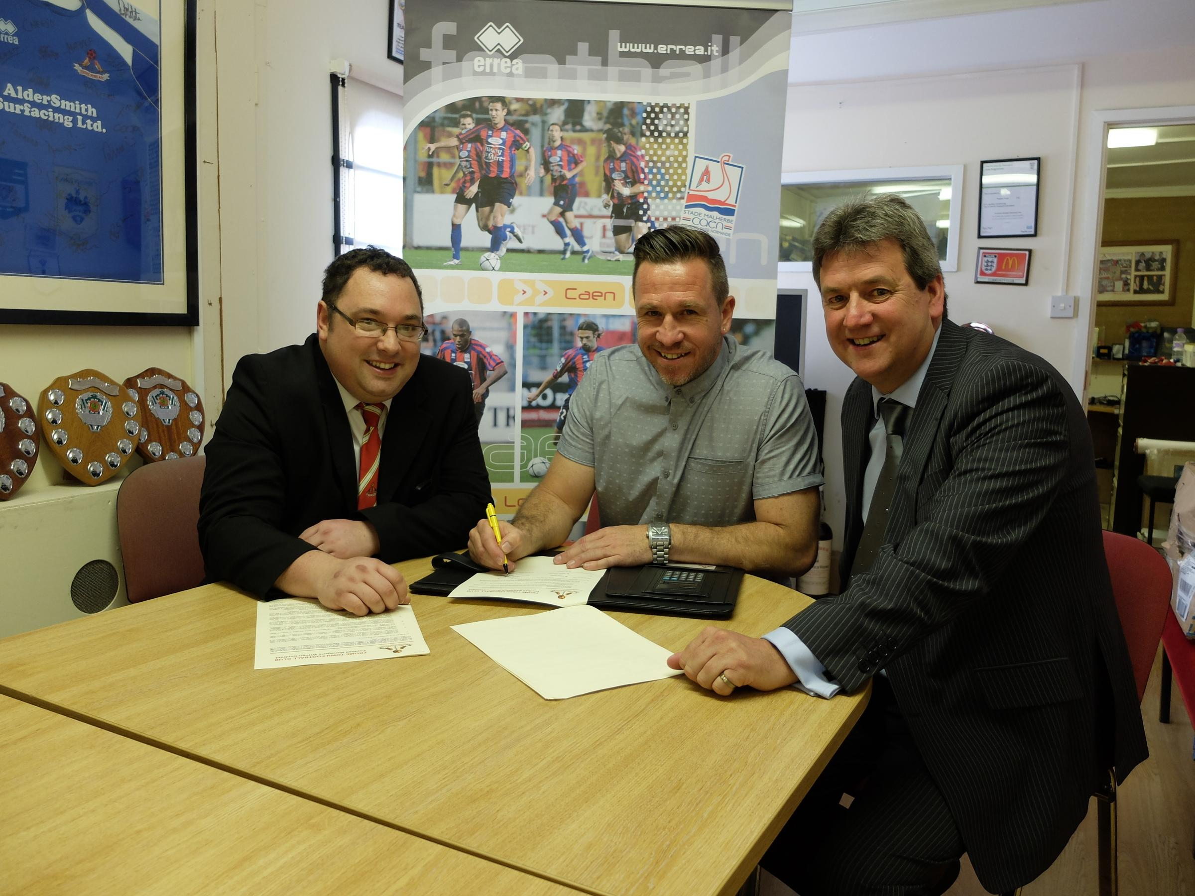 Frome Town boss Adrian Foster (centre) signs his new two-year deal with chairman Jeremy Alderman (right) and secretary Ian Pearce