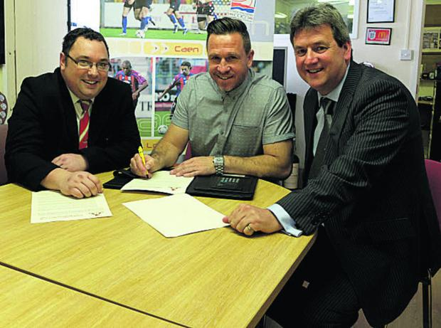 Adrian Foster signing his contract with chairman Jeremy Alderman (right) and club secretary Ian Pearce (left)
