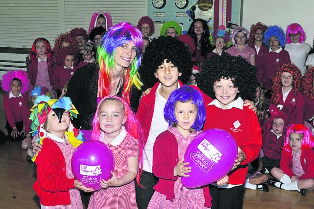 Gemma Hector of Apple a Day Supply, which organised the Wig Wednesday charity event in aid of CLIC Sargent, with Betty, Brooke, Tilly, Mete, Bradley and other pupils at Walwayne Court Primary School