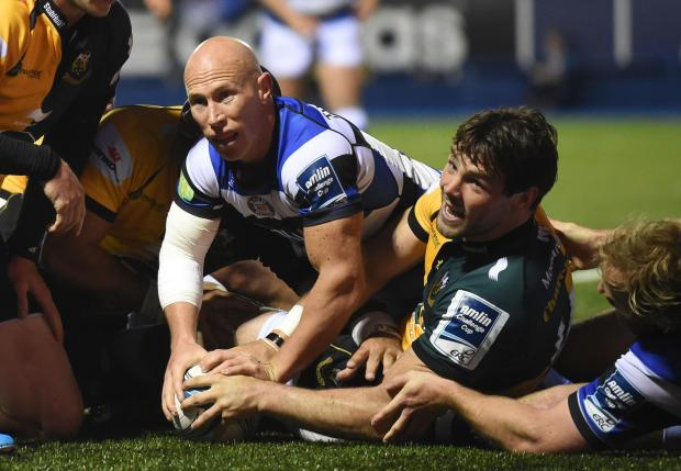 Northampton Saints' Ben Foden (right) scores a try despite the efforts of Bath Rugby's Peter Stringer (left)