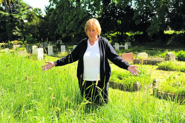 Mary Holloway, who has relatives buried in Trowbridge Cemetery, is unhappy with the unkempt grass       Photo: Trevor Porter