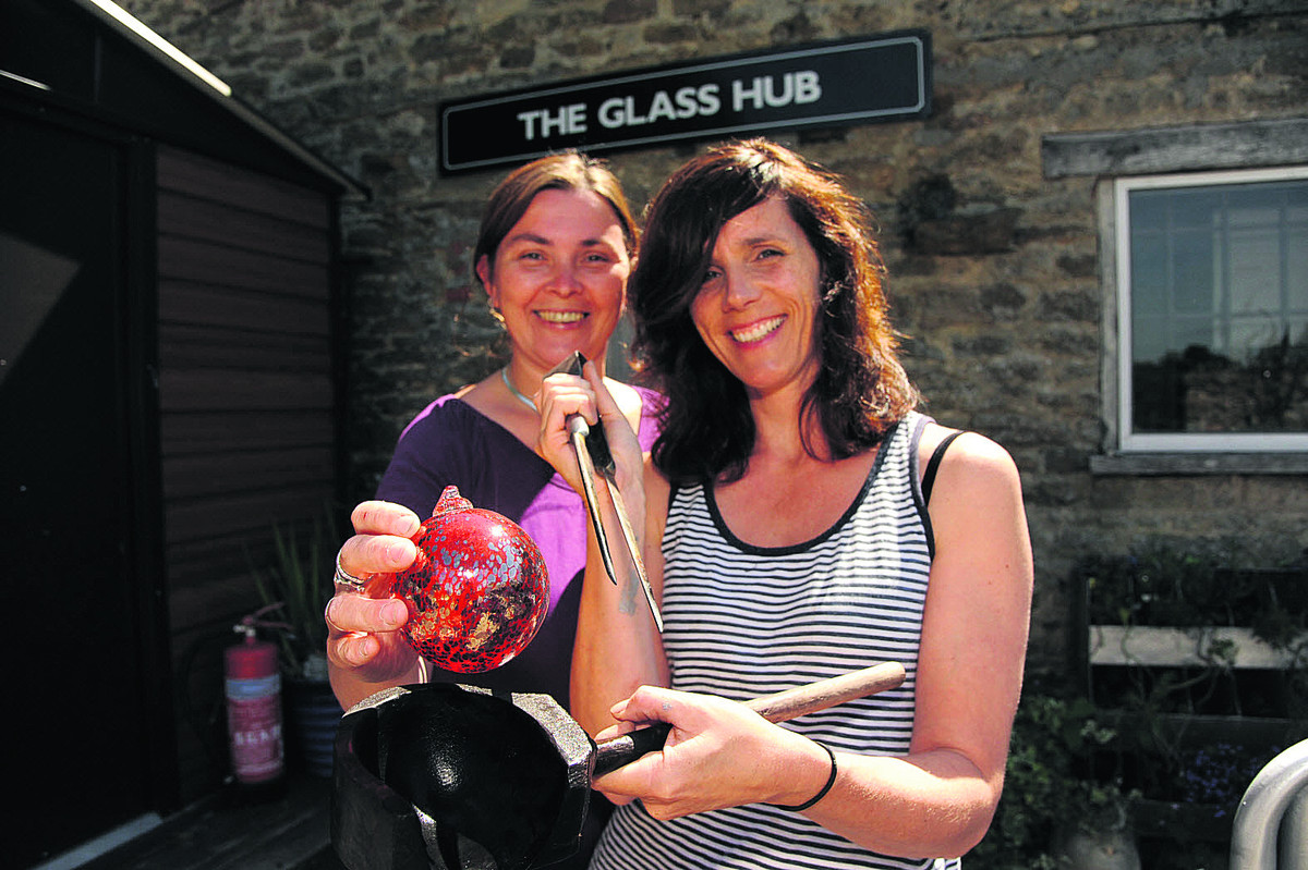 Glassblowers Helga Watkins-Baker and KT Yun at their Stowford studio with a glass sphere, a block and a jack. They will be at Glastonbury with a glassblowing demonstration showing how these tool are used