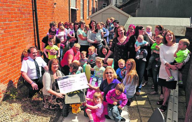 Jane Wickham of Sally Tots, centre front, hands over the cheque to Stepping Stones co-ordinator Barbara Jensen