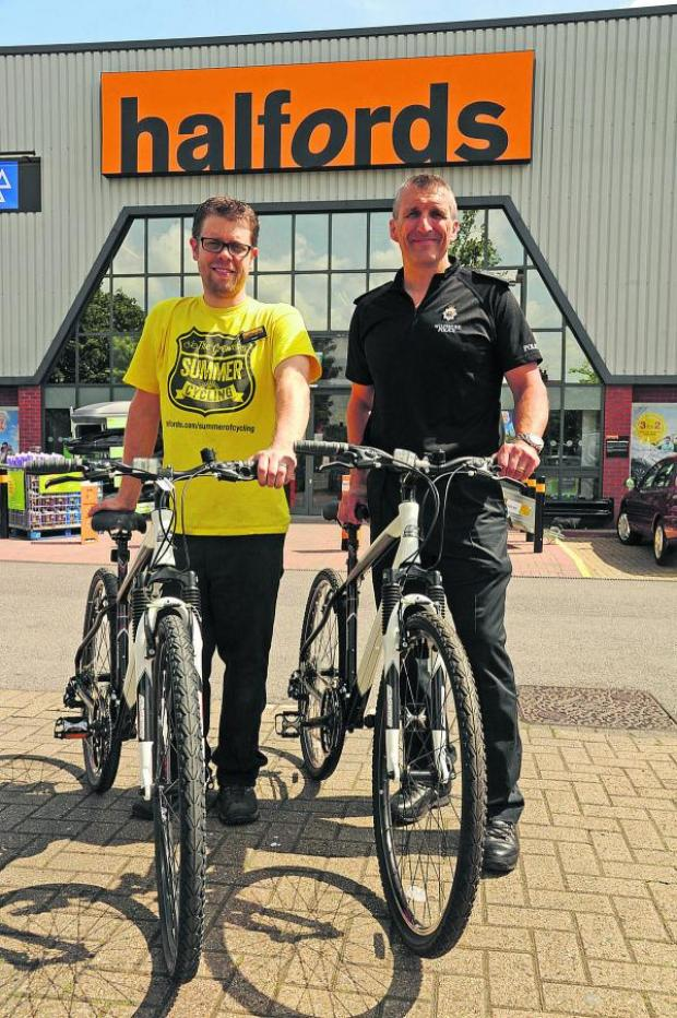 Wiltshire Times: Adam Leitch, of Halfords, hands over two bikes to Inspector Chris Chammings
