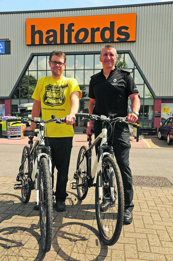 Adam Leitch, of Halfords, hands over two bikes to Inspector Chris Chammings