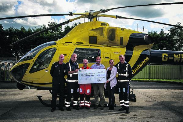David Betteridge and Maria Badder present £12,000 to a Wiltshire Air Ambulance crew