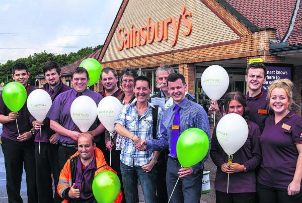 Doorway director Lisa Lewis with Sainsbury's duty manager Dan Hulland, staff and the charity's volunteers