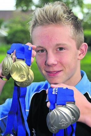 Jordan Ludlam shows off his haul of six national age group championship medals at home this week