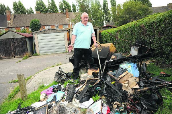 James Burrell with the burnt remains of the contents of his garage